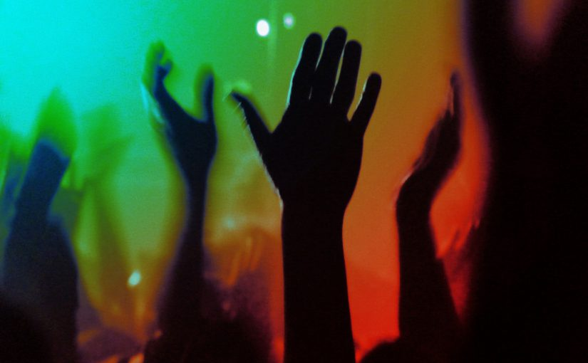 raised hands in colored lights at concert